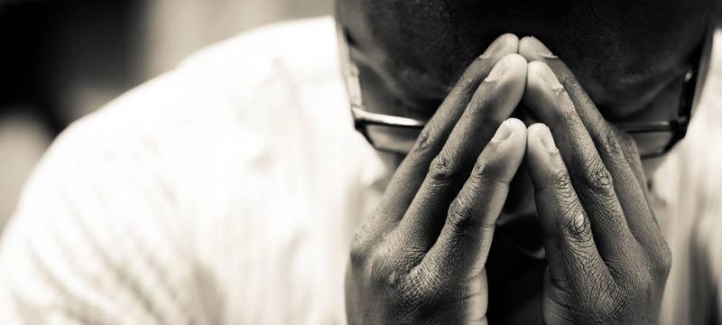 Hombre en posicion de oracion orando a Dios