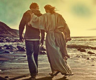 Joven camina con Jesus en una playa