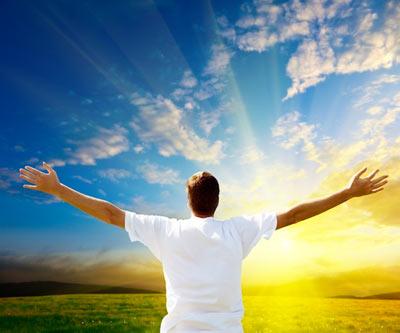 Joven extiende sus brazos frente a Dios
