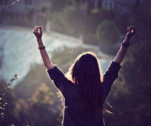 Mujer feliz levantando sus manos en un amanecer