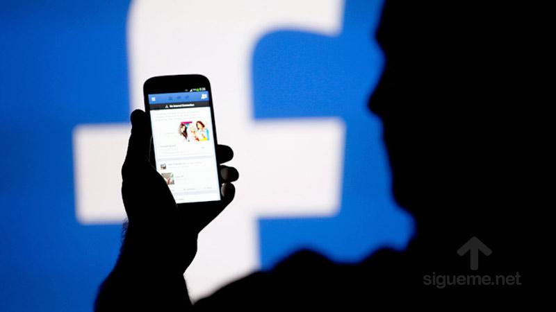 Persona mirando cuenta de Facebook desde smartphone