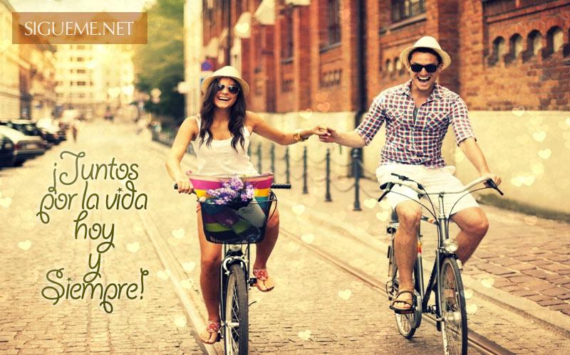 jovenes enamorados en bicicleta tomados de la mano