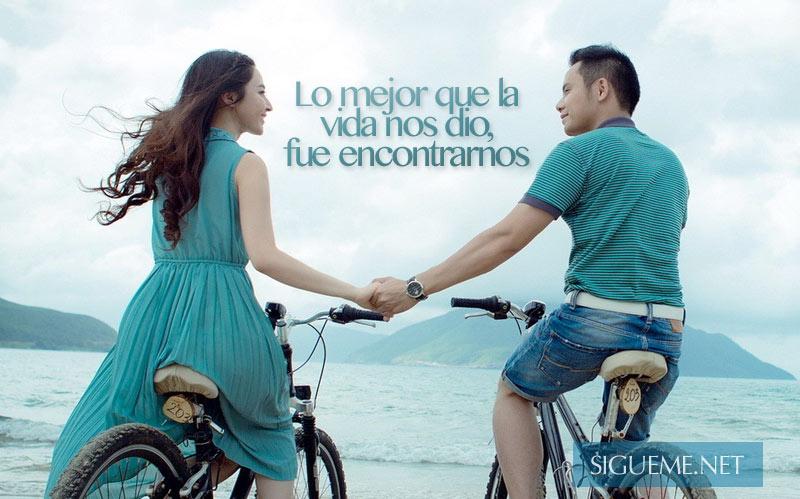 Dos jovenes en bicicletas frente al mar tomandose de la mano