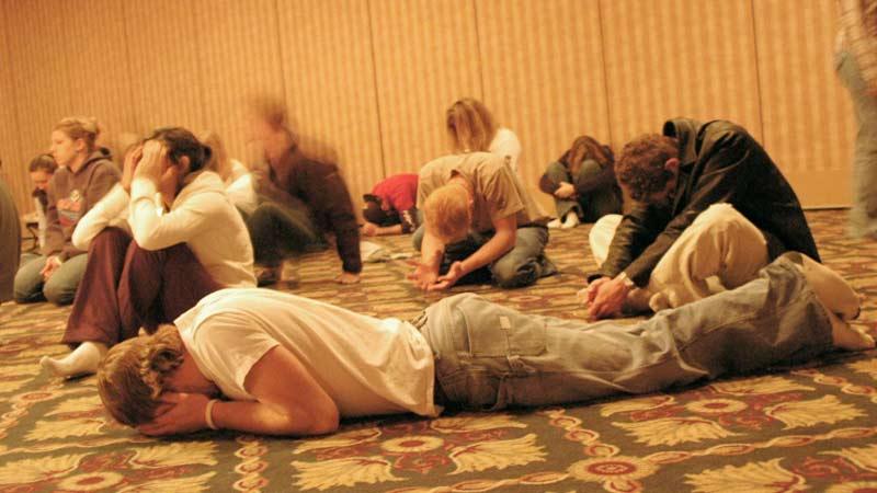 Cristianos orando postrados ante Dios