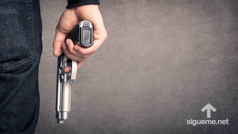 Hombre empuñando un arma de fuego en su mano