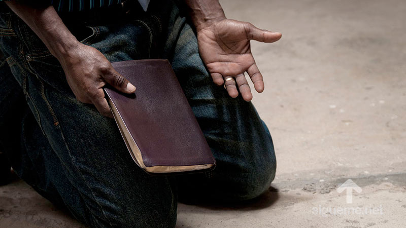 Hombre postrado sobre sus rodillas orando a Dios