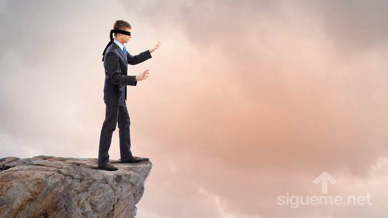 Hombre con ojos vendados frente a precipicio, concepto negar a Dios, incredulidad, ateismo