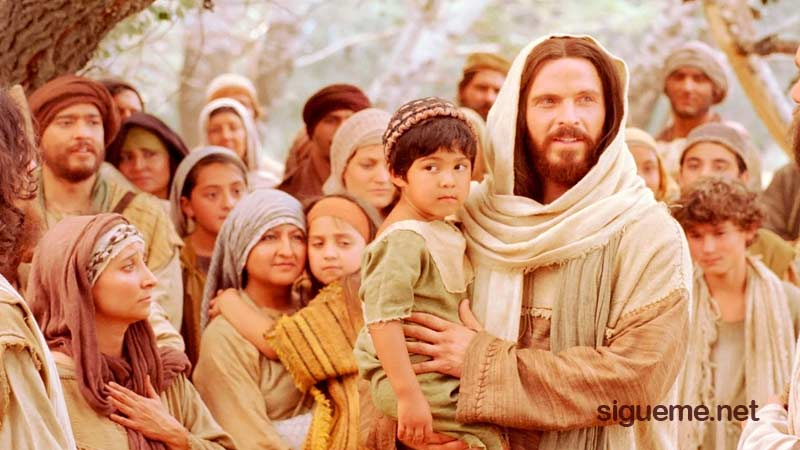 Jesus con un niño en brazos, el dijo, dejen venir los niños a mi