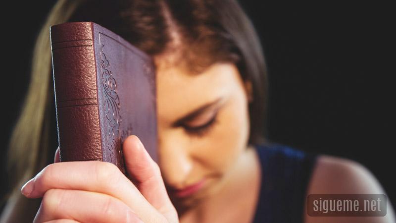 Una joven con su Biblia orando a Dios