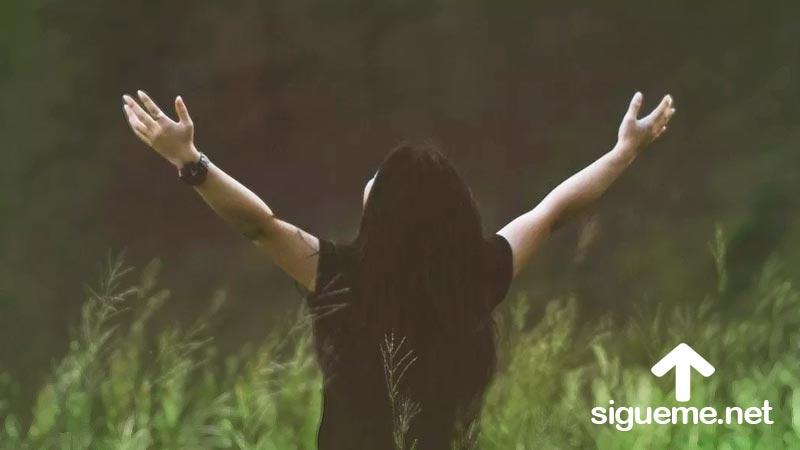 Joven cristiana levanta sus brazos en clamor a Dios