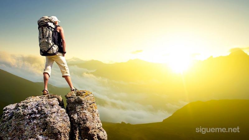 Joven en la cumbre de una montaña viendo el amanecer
