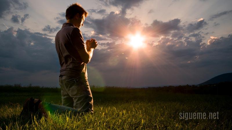 Joven de rodillas orando ante Dios