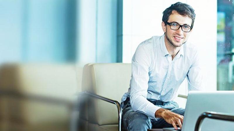Joven empresario con laptop sonriendo