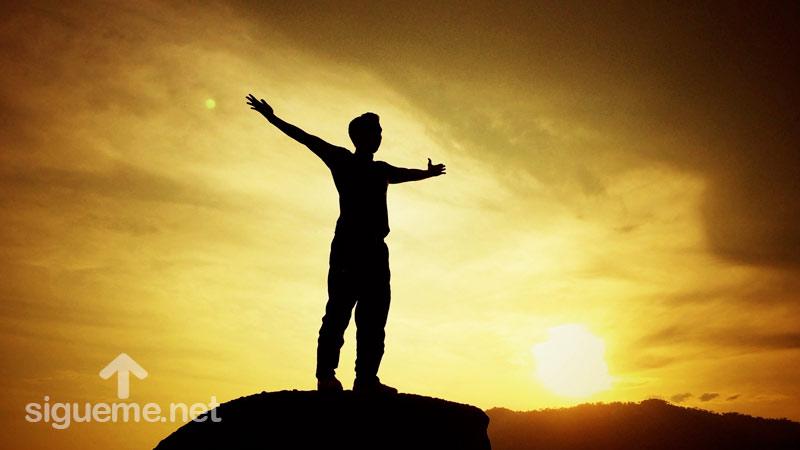 joven cristiano en la cima, con los brazos extendidos, libre