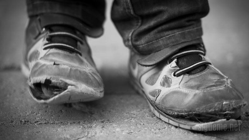 Joven pobre con el calzado roto