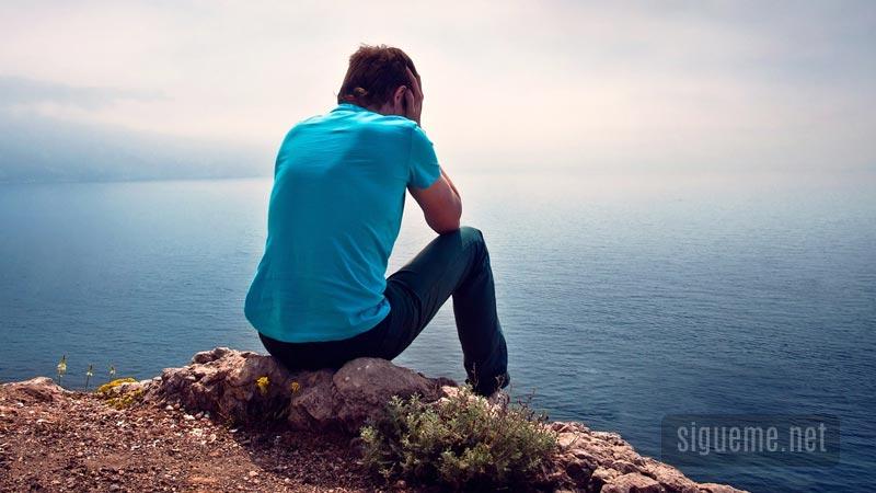 Joven sentado frente al mar preocupado