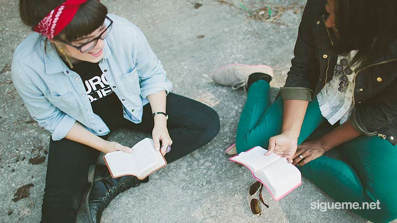 Jovenes cristianos leyendo la biblia sentados en el piso