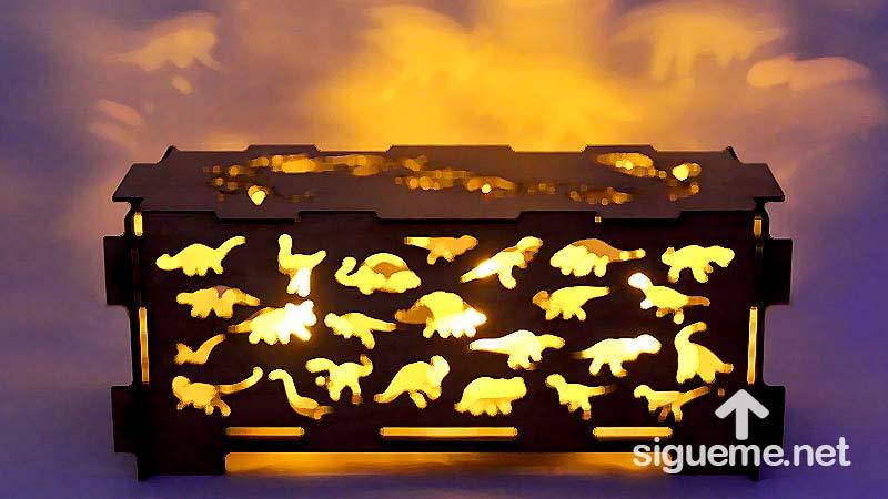 Una caja con iluminacion interna con figuras de dinosaurios