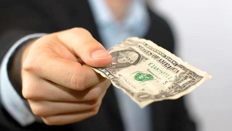 Mano sosteniendo, entregando billete de un dolar