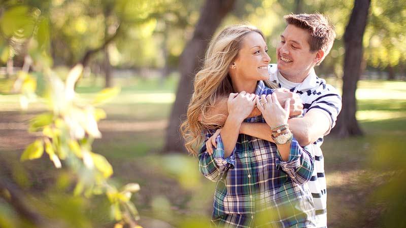 Matrimonio Joven sonriendo abrazados al aire libre