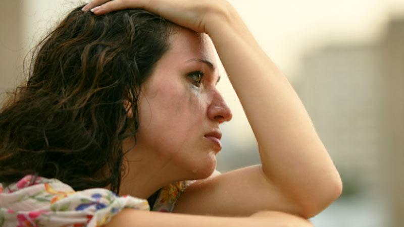 Mujer llorando mirando por una ventana triste