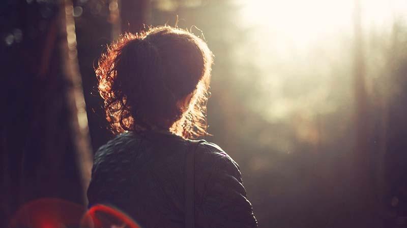Mujer contempla el amanecer en paz en medio del bosque