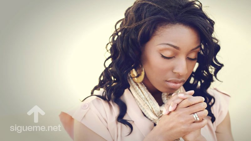 Mujer orando a Dios uniendo sus manos