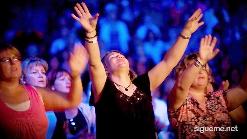 Mujeres cristianas adoran a Dios con manos alzadas en una reunion
