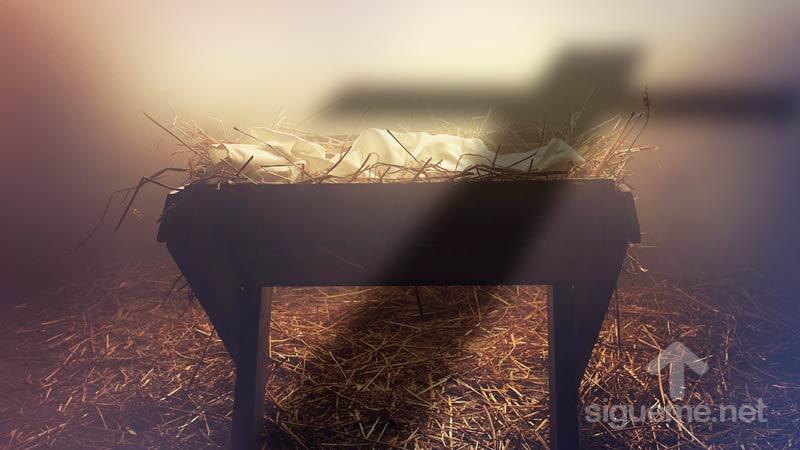 La cuna de Jesus en el pesebre atravesado por la sombra de una cruz