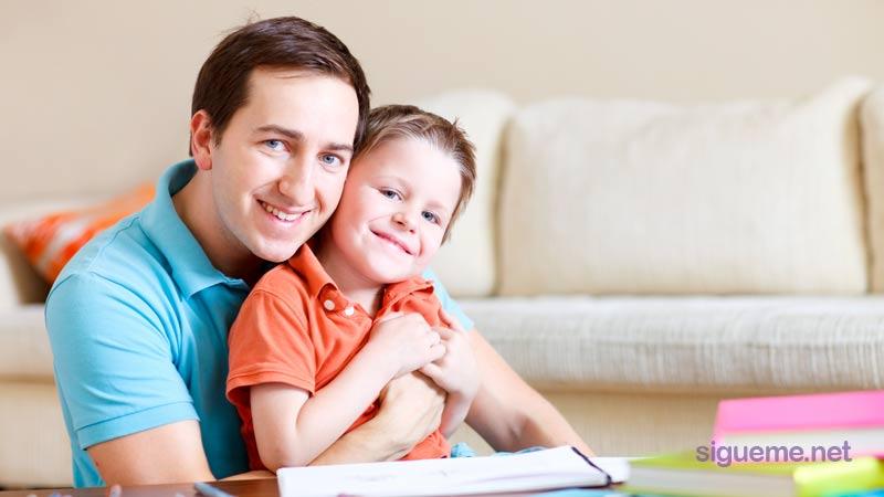 Papa abrazado junto a su hijo y sonriendo