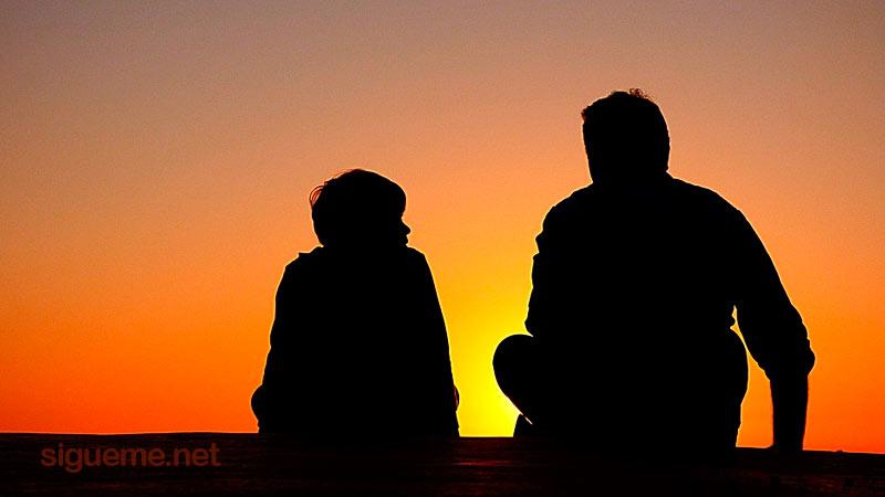 Padre e su hijo hablando juntos en el amanecer