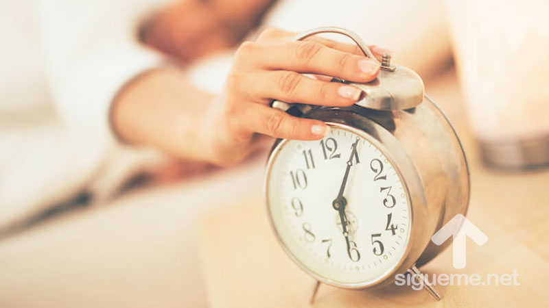 Persona despertando de su sueño apaga despertador