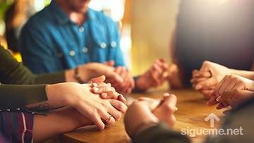 Grupo de cristianos orando a Dios tomados de las manos