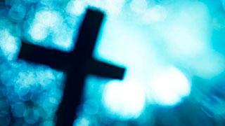 Cruz de Cristo difusa entre luces