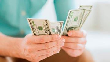 Hombre con billetes de Dólar en sus manos