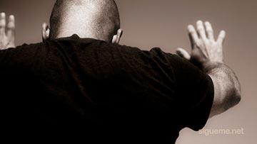 Hombre cristiano orando a Dios con sus manos en alto