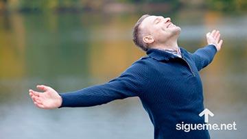 Hombre cristiano sonriendo con los brazos extendidos agradecido a Dios al aire libre