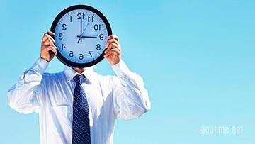 Hombre cubre su rostro con un reloj concepto tiempo