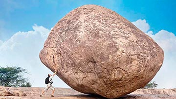 Hombre moviendo, empujando una gran roca