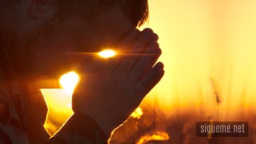 Hombre cristiano orando a Dios al amanecer