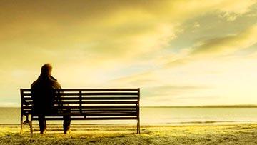 Hombre solo, sentado mirando el horizonte en soledad