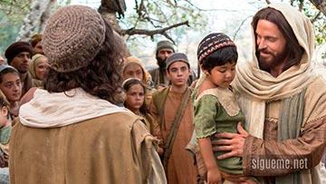 Jesus tomando a un niño en sus brazos ante la multitud