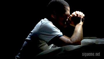 Joven cristiano orando a Dios en su cuarto de oracion