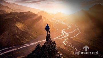 Joven conquistando la cumbre y contemplando el amanecer