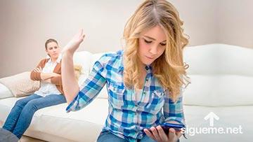 Joven mujer mira su celular y no le presta atencion a lo que dice su madre