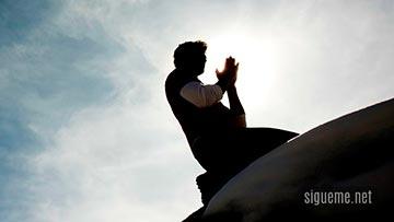 Joven arrodillado delante de Dios en oracion