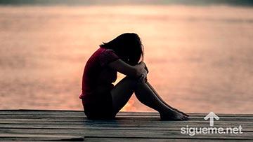 Joven mujer triste cubriendose el rostros