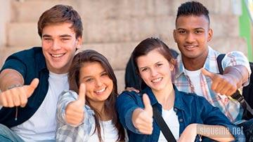 Jovenes sonriendo con pulgares arriba en actitud positiva