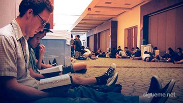 Grupo de jovenes cristianos de una iglesia lleen la Biblia sentadps en el piso