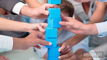 Equipo de lideres sosteniendo y aportando las partes de una estructura